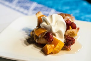 cranberry butternut squash bread pudding with maple syrup and whipped cream